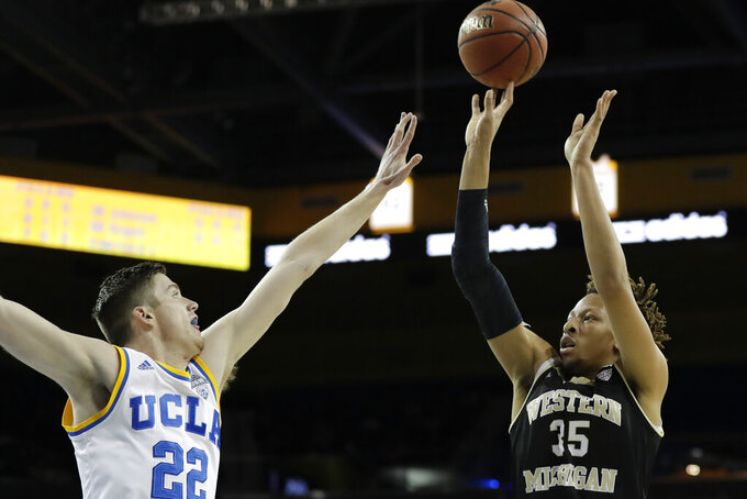 FILE - In this Dec. 21, 2016, file photo, Western Michigan forward Brandon Johnson, right, shoots over UCLA forward T.J. Leaf during the first half of an NCAA college basketball game in Los Angeles. Minnesota has added two accomplished front court players to the roster, bringing in Liam Robbins from Drake and Brandon Johnson from Western Michigan. The Gophers announced the signing of both big men on Wednesday, April 15, 2020. (AP Photo/Chris Carlson, File)