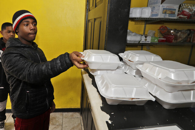 Tommy Barnes, 14, picks up a free meal at GoodFellas Barbecue Restaurant, Friday, March 27, 2020, in Cleveland Heights, Ohio. The restaurant is serving about 200 free meals to children per day. The meals feed the kids in the community who have depended on food at school but because of the coronavirus haven't been able to get their lunches. (AP Photo/Tony Dejak)