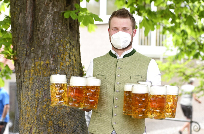 """A waiter with face covering protection carries glasses of beer for customers in the beer garden at the """"Gasthof zur Br'cke"""" during a press event for the opening of the beer garden season, in Kaufering, Germany, Monday May 10, 2021.  As of May 10, outdoor restaurants are allowed to reopen in Bavarian counties and cities. (Tobias Hase/dpa via AP)"""