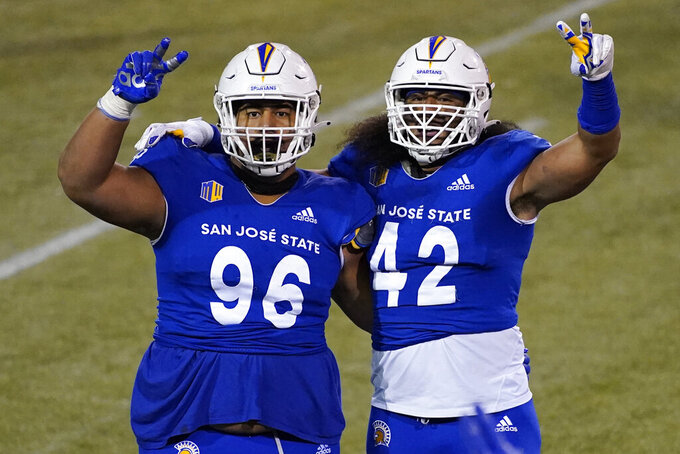 San Jose State defensive lineman Jay Kakiva (96) and defensive end Viliami Fehoko (42) celebrate as the team leads Nevada near the end of an NCAA college football game Friday, Dec. 11, 2020, in Las Vegas. (AP Photo/John Locher)