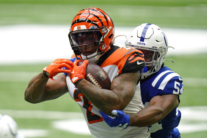 Cincinnati Bengals' Joe Mixon (28) is tackled by Indianapolis Colts' Anthony Walker (54) during the first half of an NFL football game, Sunday, Oct. 18, 2020, in Indianapolis. (AP Photo/AJ Mast)