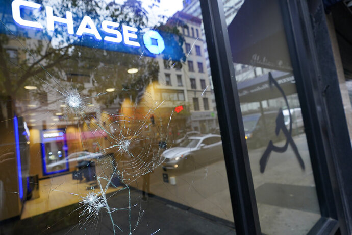 A graffiti hammer and sickle is seen next to broken glass at a Chase ATM, Wednesday, Oct. 28, 2020, on Court Street in the Boerum Hill neighborhood of the Brooklyn borough of New York. Demonstrators protesting the police shooting of a Black man in Philadelphia broke store windows, set fires and vandalized police cars in Brooklyn Tuesday night, police said. (AP Photo/Mary Altaffer)