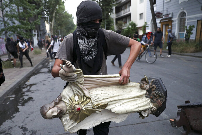 A masked demonstrator carries a statue of Jesus Christ that he took from a church to be added to a barricade, in Santiago, Chile, Friday, Nov. 8, 2019.  Chile's president on Thursday announced measures to increase security and toughen sanctions for vandalism following three weeks of protests that have left at least 20 dead. (AP Photo/Esteban Felix)