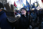 Protesters shouts slogans and wave flags during a rally in front of the parliament building to protest against changes to laws governing the sale of farmland, in Kyiv, Ukraine, Thursday, Feb. 6, 2020. Scuffles broke out inside parliament as lawmakers debated changes to laws restricting sales of farmland. (AP Photo/Efrem Lukatsky)