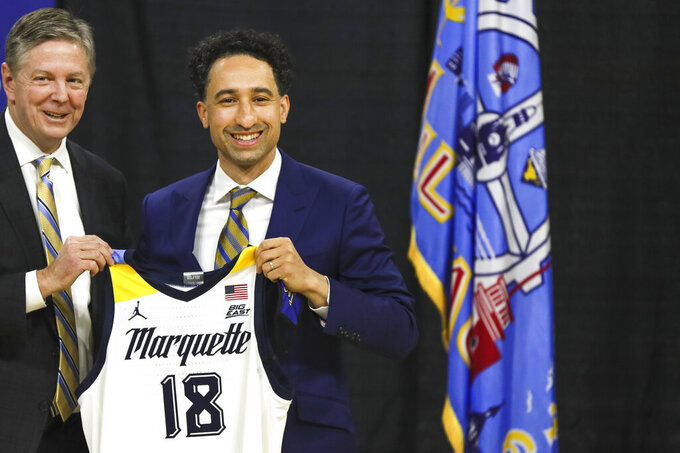 Bill Scholl, left, Marquette vice president and director of athletics, gives Shaka Smart a jersey Monday, March 29, 2021, at the Al McGuire Center in Milwaukee. Smart is the new NCAA college head men's basketball coach at Marquette. (Ebony Cox/Milwaukee Journal-Sentinel via AP)