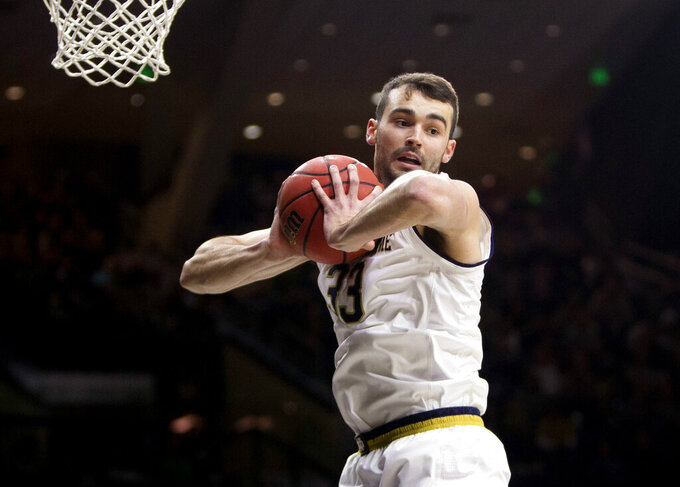 FILE - In this Feb. 23, 2019, file photo, Notre Dame's John Mooney (33) grabs a rebound during an NCAA college basketball game against Virginia Tech in South Bend, Ind. Notre Dame men's basketball coach Mike Brey feels confident as long as Mooney keeps making double-doubles and his teammates stay healthy. Factoring in his 20 double-doubles, the 6-foot-9 senior Mooney averaged team highs of 14.1 points and 11.2 rebounds for the injury-plagued Irish. (AP Photo/Robert Franklin, File)