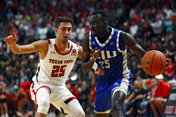 Eastern Illinois' Deang Deang (25) drives the ball around Texas Tech's Davide Moretti (25) during the first half of an NCAA college basketball game Tuesday, Nov. 5, 2019, in Lubbock, Texas. (AP Photo/Brad Tollefson)