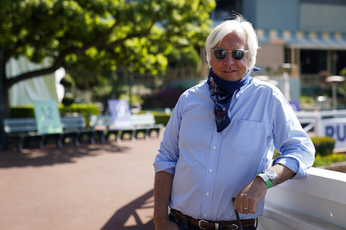 In this Friday, May 22, 2020 photo, Bob Baffert, two-time Triple Crown-winning trainer, lowers his bandana during an interview while keeping his distance at Santa Anita Park in Arcadia, Calif. Horse racing returned to the track after being idled for one and a half months because of public health officials' concerns about the coronavirus pandemic. (AP Photo/Ashley Landis)