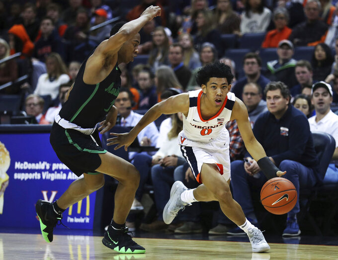 Virginia's guard Kihei Clark (0) drives past Marshall's Taevion Kinsey (1) in the first half of an NCAA college basketball game on Monday, Dec. 31, 2018, in Charlottesville, Va. (AP Photo/Zack Wajsgras)