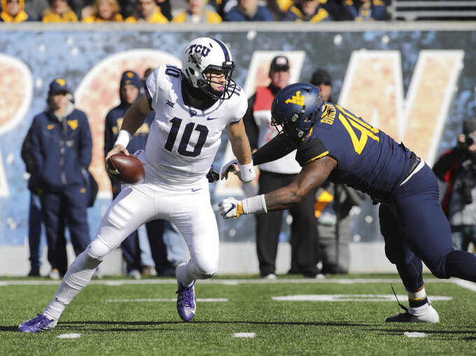 TCU quarterback Michael Collins (10) is nearly sacked by West Virginia defensive lineman Kenny Bigelow Jr. (40) during the first half of an NCAA college football game Saturday, Nov. 10, 2018, in Morgantown, W.Va. (AP Photo/Raymond Thompson)