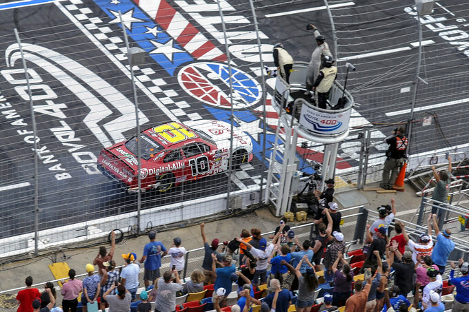 AJ Allmendinger (10) gets the checkered flag to win a NASCAR Xfinity Series auto race at Charlotte Motor Speedway, Saturday, Sept. 28, 2019, in Concord, N.C. (AP Photo/Mike McCarn)