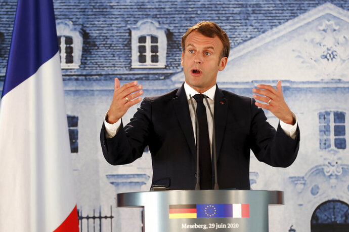 French President Emmanuel Macron gestures as he gives a press conference after a bilateral meeting with German Chancellor Angela Merkel, at the German government's guest house Meseberg Castle in Gransee near Berlin, Germany, Monday, June 29 2020. The meeting takes place ahead of Germany's EU Council Presidency in the second half of 2020. (Hayoung Jeon, Pool via AP)