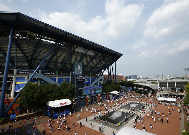 FILE - In this Aug. 27, 2018, file photo, fans walk outside of Arthur Ashe Stadium during the first round of the U.S. Open tennis tournament in New York. Governor Andrew Cuomo announced, Tuesday, June 16, 2020, that the U.S. Open will be played in Queens from Aug. 31 to Sept. 13, but without fans in attendance. (AP Photo/Jason DeCrow, File)
