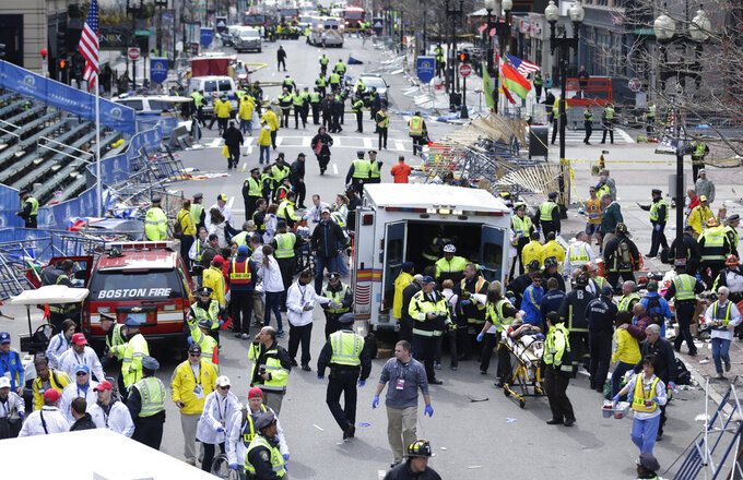 FILE - In this April 15, 2013, file photo, medical workers aid injured people at the finish line of the 2013 Boston Marathon following an explosion in Boston. (AP Photo/Charles Krupa, File)