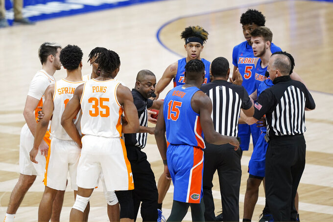 Tennessee and Florida players are separated after a foul by Florida's Omar Payne (5) in the second half of an NCAA college basketball game in the Southeastern Conference Tournament Friday, March 12, 2021, in Nashville, Tenn. Payne was ejected from the game. (AP Photo/Mark Humphrey)