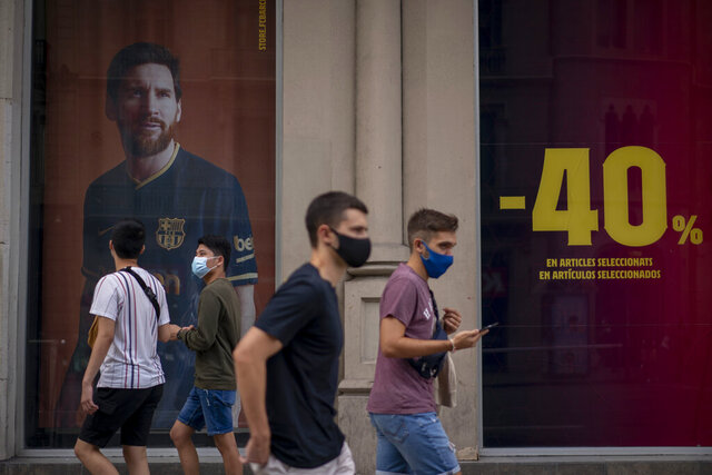 People walk past a poster with the image of Barcelona soccer player Lionel Messi at a F.C. Barcelona store in Barcelona, Spain on Tuesday, Sept. 1, 2020. Barcelona is banking on a face-to-face meeting with Lionel Messi to try to convince him to stay. Talks with Messi's father-agent are expected this week in Barcelona but the club also hopes to sit down with the player himself. (AP Photo/Emilio Morenatti)
