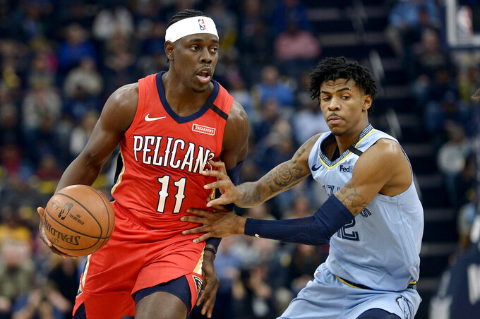 """FILE - In this Monday, Jan. 20, 2020 file photo, New Orleans Pelicans guard Jrue Holiday (11) handles the ball against Memphis Grizzlies guard Ja Morant in the first half of an NBA basketball game in Memphis, Tenn. The unusual resumption of the NBA season during the coronavirus pandemic is making mental health a priority. Pelicans guard Jrue Holiday expects basketball to be the easy part of living in the NBA's """"bubble"""" when 22 teams gather in Central Florida to resume their suspended seasons later this month. (AP Photo/Brandon Dill, File)"""