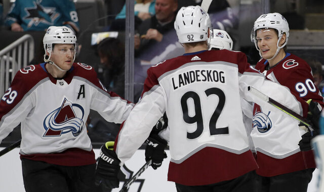 Colorado Avalanche center Vladislav Namestnikov, right, celebrates with Gabriel Landeskog (92) and Nathan MacKinnon, left, after scoring a goal against the San Jose Sharks in the second period of an NHL hockey game Sunday, March 8, 2020, in San Jose, Calif. (AP Photo/Ben Margot)