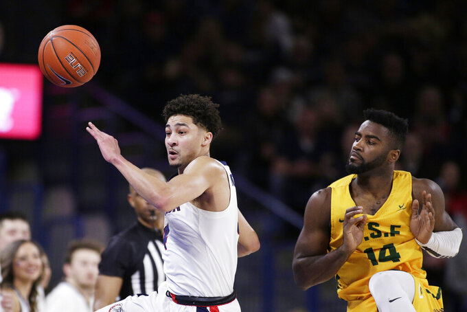 Gonzaga guard Ryan Woolridge, left, and San Francisco guard Charles Minlend go after a San Francisco inbound pass during the first half of an NCAA college basketball game in Spokane, Wash., Thursday, Feb. 20, 2020. (AP Photo/Young Kwak)