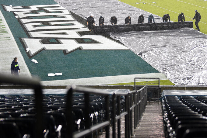 Grounds crew workers pull up a tarp covering Lincoln Financial Field before an NFL football game between the Philadelphia Eagles and the Seattle Seahawks, Monday, Nov. 30, 2020, in Philadelphia. (AP Photo/Derik Hamilton)