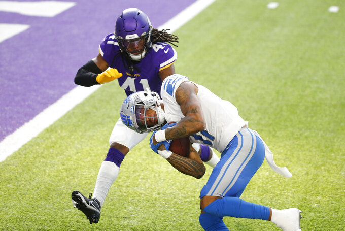 Detroit Lions wide receiver Marvin Jones Jr. scores on a 15-yard touchdown reception ahead of Minnesota Vikings safety Anthony Harris (41) during the first half of an NFL football game, Sunday, Nov. 8, 2020, in Minneapolis. (AP Photo/Bruce Kluckhohn)