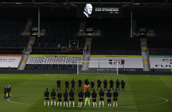 Players from both sides observe a minute's silence to honor Britain's Prince Philip, Duke of Edinburgh, after the announcement of the death today, before the English Premier League soccer match between Fulham and Wolverhampton Wanderers at Craven Cottage stadium in London, England, Friday, April 9, 2021.(Andrew Couldridge/Pool via AP)