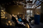 Ebony Thomas looks at her phone a she sits on a sofa inside her shattered home, in the aftermath of Hurricane Dorian, in Mclean's Town, Grand Bahama, Bahamas, Wednesday Sept. 11, 2019. The 15-year-old lost three members of her family to the Hurricane. (AP Photo/Ramon Espinosa)