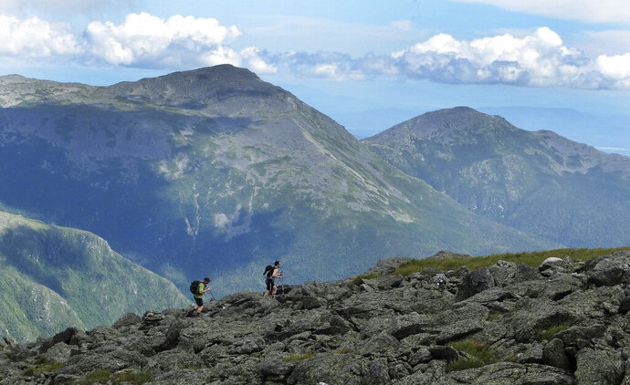 FILE - In this July 27, 2016 file photo, a pair of hikers traverse a trail on Mount Washington, N.H. New Hampshire Fish and Game officials said, Tuesday, June 18, 2019, they're likely to recommend charging an 80-year-old hiker who was rescued while trying to reach the summit of Mount Washington. James Clark, of Dublin, Ohio, was found Friday, June 14, 2019, immobile in the fetal position with signs of hypothermia. Lt. Mark Ober said his agency would likely recommend that Clark pay for the cost of his rescue since he was unprepared for the hike. He didn't have the right clothing to make the ascent in freezing rain and temperatures that were below freezing. (AP Photo/Jim Cole, File)