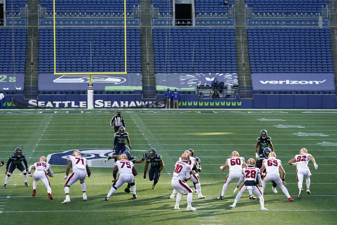 San Francisco 49ers quarterback Jimmy Garoppolo (10) drops to pass against the Seattle Seahawks in an empty CenturyLink Field due to the coronavirus during the first half of an NFL football game, Sunday, Nov. 1, 2020, in Seattle. (AP Photo/Elaine Thompson)