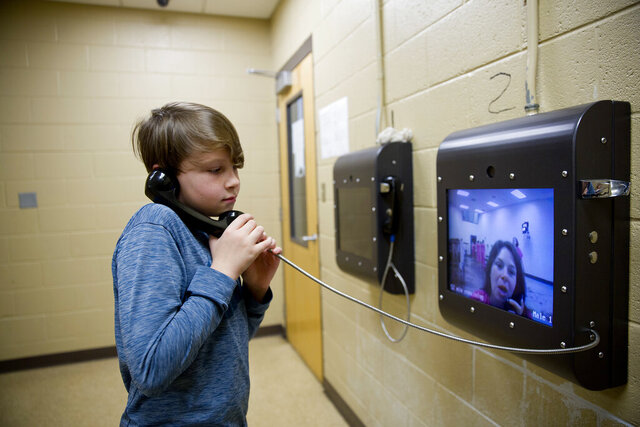 FILE - In this March 28, 2018, file photo, Robbie Wilson, 10, talks with his mother Krystle Sweat in a video conference as he visits her in the Campbell County Jail in Jacksboro, Tenn. The San Juan County Adult Detention Center, a northwestern New Mexico jail, announced in January 2020, it would join some jails in Tennessee and no longer allow family and friends to visit detainees in person and will now offer only phone or online video chats. (AP Photo/David Goldman, File)