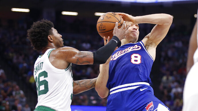 Boston Celtics guard Marcus Smart, left, fouls Sacramento Kings guard Bogdan Bogdanovic during the first half of an NBA basketball game in Sunday, Nov. 17, 2019. (AP Photo/Rich Pedroncelli)