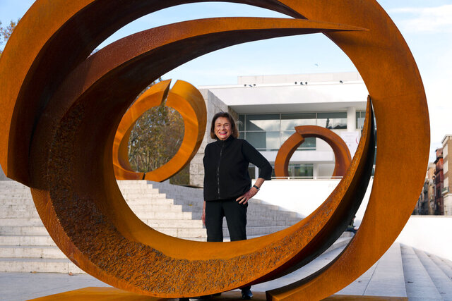 FILE -- In this Dec. 2, 2014 file photo U.S. artist and sculptor Beverly Pepper poses with her latest sculptures part of the 'Curvae in Curvae' series on display in front of the Ara Pacis Museum in downtown Rome. Pepper, an acclaimed American sculptor, died Wednesday at her home in Todi, Italy.  She was 97.  (AP Photo/Domenico Stinellis)