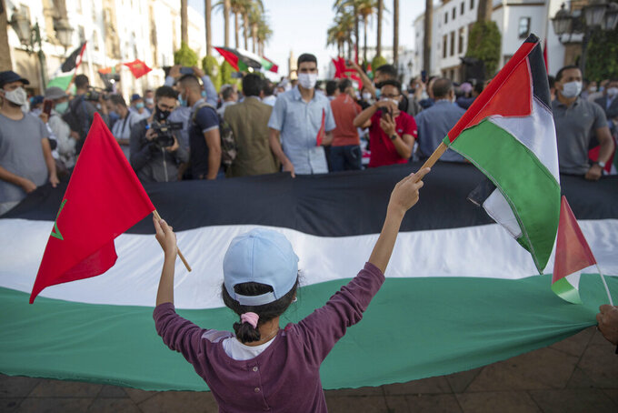 A young girl waves a Moroccan and a Palestinian flag during a protest against normalizing relations with Israel, in Rabat, Morocco, Friday, Sept. 18, 2020. Despite a government ban on large gatherings aimed at preventing the spread of the coronavirus, scores of Moroccans staged a protest outside parliament building in the capital Rabat on Friday to denounce Arab normalization agreements with Israel. (AP Photo/Mosa'ab Elshamy)