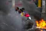 FILE - In this Sept. 17, 2019 file photo, a moto-taxi driver takes two passengers past a burning barricade during a protest against fuel shortages in Port-au-Prince, Haiti. Haiti's economy, already fragile when the new round of protests began in mid-Sept., is in deep trouble with spiraling inflation and dwindling supplies, including fuel. (AP Photo/Dieu Nalio Chery, File)