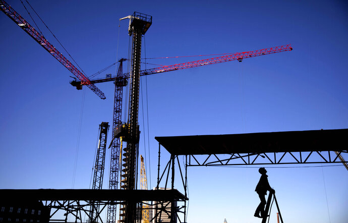 FILE - In this Oct. 23, 2019, file photo a worker climbs a ladder as cranes work the construction site for the new corporate headquarters of Norfolk Southern in Atlanta. On Wednesday, Nov. 27, the Federal Reserve releases its latest