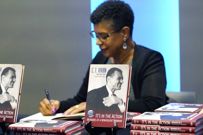 Denise Morse autographs a book about her father, the late C.T. Vivian, on Wednesday, May 26, 2021, at the Mississippi Civil Rights Museum in Jackson, Miss. Mississippi's capital city honored the civil rights activism of the late Rev. C.T. Vivian 60 years after he and other Freedom Riders were arrested upon arrival in Jackson as they challenged segregation in interstate buses and bus terminals across the American South. Jackson's current mayor declared Wednesday as C.T. Vivian Day. (AP Photo/Rogelio V. Solis)