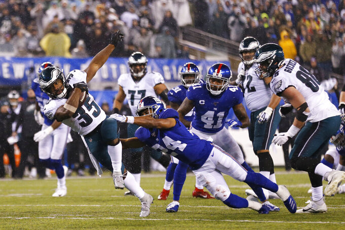 Philadelphia Eagles running back Boston Scott (35) runs with the ball in front of New York Giants cornerback Julian Love (24) in the second half of an NFL football game, Sunday, Dec. 29, 2019, in East Rutherford, N.J. (AP Photo/Adam Hunger)