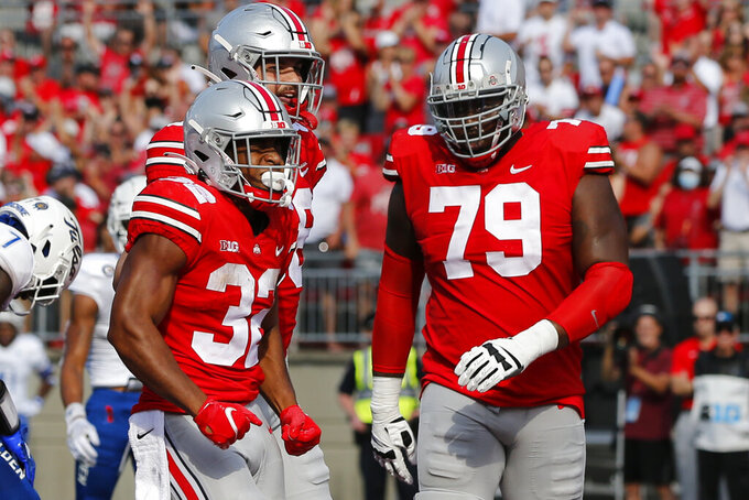 Ohio State running back TreVeyon Henderson, left, celebrates his touchdown against Tulsa with teammate Dawand Jones during the first half of an NCAA college football game Saturday, Sept. 18, 2021, in Columbus, Ohio. (AP Photo/Jay LaPrete)