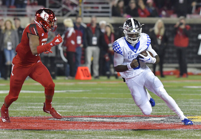 Kentucky quarterback Terry Wilson (3) is pursued by Louisville safety Dee Smith (11) during the first half of an NCAA college football game in Louisville, Ky., Saturday, Nov. 24, 2018. (AP Photo/Timothy D. Easley)