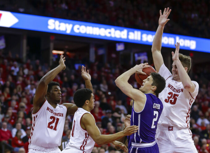 Northwestern's Ryan Greer (2) goes up against Wisconsin's Khalil Iverson (21), D'Mitrik Trice and Nate Reuvers (35) during the first half of an NCAA college basketball game Saturday, Jan. 26, 2019, in Madison, Wis. (AP Photo/Andy Manis)