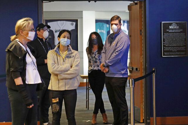 Former Seattle Mariners baseball player Dan Wilson, right, and his wife Annie Wilson wear masks as they wait with others in line to donate blood at a pop-up blood donor event at the Mariners' ballpark Monday, April 13, 2020, in Seattle. The Mariners teamed with Bloodworks Northwest for the appointment-only donor event to help ensure the region's blood supply is maintained during the coronavirus outbreak. Originally schedule for three weeks, because appointments filled so quickly the collection effort has been extended to the end of May. (AP Photo/Elaine Thompson)
