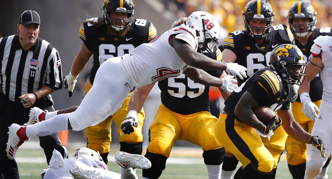 Iowa running back Mekhi Sargent runs from Northern Illinois linebacker Antonio Jones-Davis, left, during the first half of an NCAA college football game, Saturday, Sept. 1, 2018, in Iowa City, Iowa. (AP Photo/Charlie Neibergall)