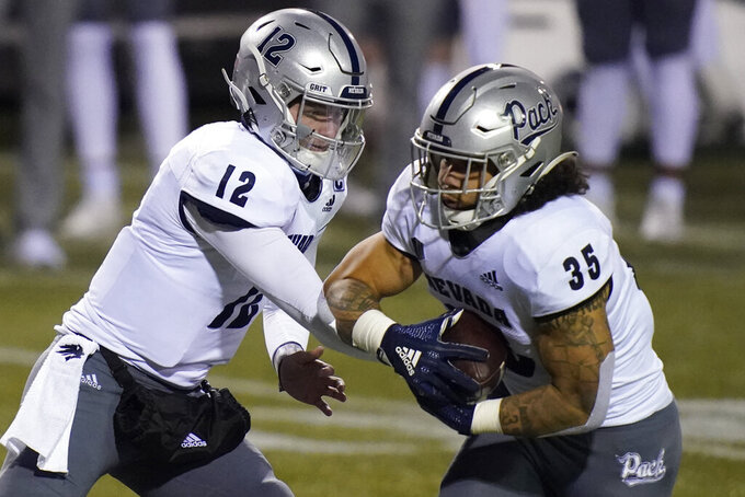 Nevada quarterback Carson Strong (12) hands off the ball to running back Toa Taua (35) during the first half of the team's NCAA college football game against San Jose State, Friday, Dec. 11, 2020, in Las Vegas. (AP Photo/John Locher)