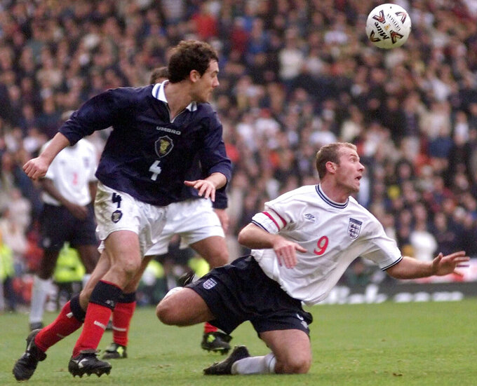 FILE- In this Saturday, Nov. 13 1999 file photo, England's soccer captain Alan Shearer, right, in action against Scotland's Christian Dailly at Glasgow's Hampden Park, Scotland, during their soccer Euro 2000 qualifier, which England won 2-0.  While England opened Euro 2020 with a win over Croatia, Scotland lost to the Czech Republic in its first men's tournament game of the 21st century, but international soccer's oldest rivalry will rise again when England plays Scotland at Wembley Stadium Friday June 18, 2021. (AP Photo/Max Nash, File)