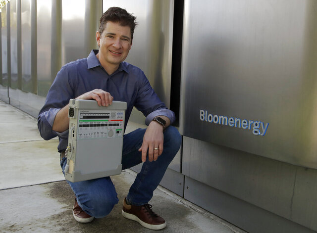 Joe Tavi, Bloom Energy senior director of manufacturing, holds a refurbished ventilator as he kneels beside fuel cells, Wednesday, April 1, 2020, in Sunnyvale, Calif. The new coronavirus outbreak has prompted companies large and small to rethink how they do business. Bloom Energy, in San Jose, Calif., makes hydrogen fuel cells. But recently, they have been refurbishing old ventilators so hospitals can use them to keep coronavirus patients alive. (AP Photo/Ben Margot)