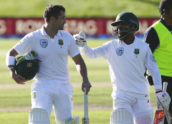 FILE - In this Wednesday, March 8, 2017 file photo, South Africa's Dean Elgar, left, is congratulated by teammate Temba Bavuma after scoring 128 not out as they leave the field following the first day's play of the first cricket test against New Zealand at University Oval, Dunedin, New Zealand. Elgar and Bavuma have been named South Africa's new cricket captains. Opening batsman Elgar will lead the team in tests. Top-order batsman Bavuma will take charge for limited-overs games and be test vice captain. They replace wicketkeeper-batsman Quinton de Kock, who stepped down from both roles. (AP Photo/Mark Baker, File)