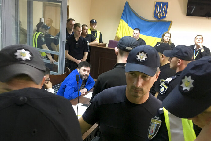 Kirill Vyshinskiy, the head of the Ukrainian office of Russia's RIA Novosti news agency in Ukraine, center, sits in a court room in Kiev, Ukraine, Friday, July 19, 2019.  Ukraine's president Volodymyr Zelenskiy released a statement Friday giving details of an impending prisoner swap with Russia, saying that Kiev is willing to release a jailed Russian journalist in exchange for a Ukrainian film director. (AP Photo/Efrem Lukatsky)