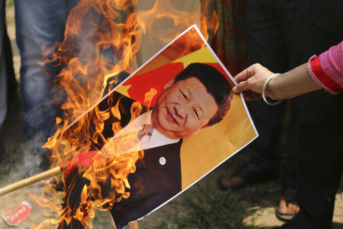 FILE - In this Wednesday, July 1, 2020, file photo, a Bharatiya Janata Party activist burns a photograph of Chinese President Xi Jinping during a protest in Jammu, India. As the escalating and bitter military standoff between India and China protracts following their bloodiest confrontation in decades in the Ladakh region in 2020, experts warn the two nuclear-armed countries can unintentionally slide into a war over the roof of the world. Both the Asian giants have accused the other of fresh provocations, including allegations of soldiers crossing into each other's territory this week and vowed to protect their territorial integrity. (AP Photo/Channi Anand, File)