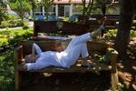 In this Jan. 3, 2019 photo, Tammy Pennington of the U.S., relaxes on a bench in the gardens of the Casa de Dom Inacio founded by spiritual healer Joao Teixeira de Faria, in Abadiania, Brazil. By all accounts, the number of visitors is way down, but the flow hasn't stopped entirely, since the arrest of the Brazilian spiritual healer who has been accused of sexual abuse by more than 250 women including his daughter. (AP Photo/Eraldo Peres)