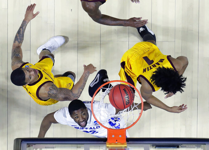 Buffalo's Dontay Caruthers, center, scores as Arizona State's Rob Edwards and Arizona State's Remy Martin (1) defend during the second half of a first round men's college basketball game in the NCAA Tournament Friday, March 22, 2019, in Tulsa, Okla. (AP Photo/Jeff Roberson)